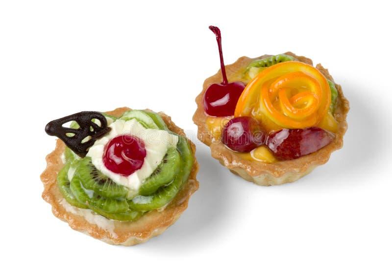 Zwei bunte Fruchtkuchen mit der Kiwi, Orange, kandierter Kirsche, Creme und Schokolade lokalisiert auf weißem Hintergrund lizenzfreie stockfotografie