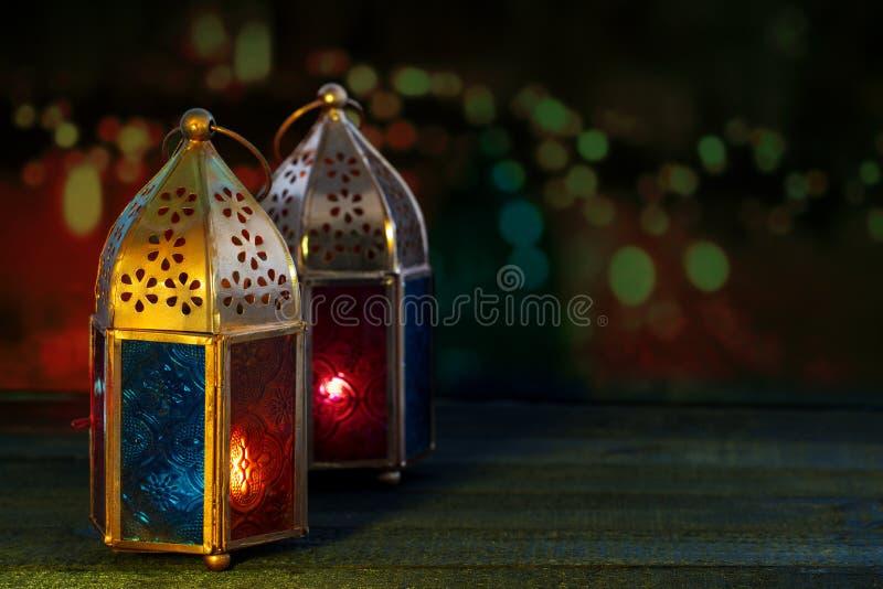 Zwei bunte orientalische Lampenlaternen brennen mit Kerzen mit Farbe lizenzfreies stockbild