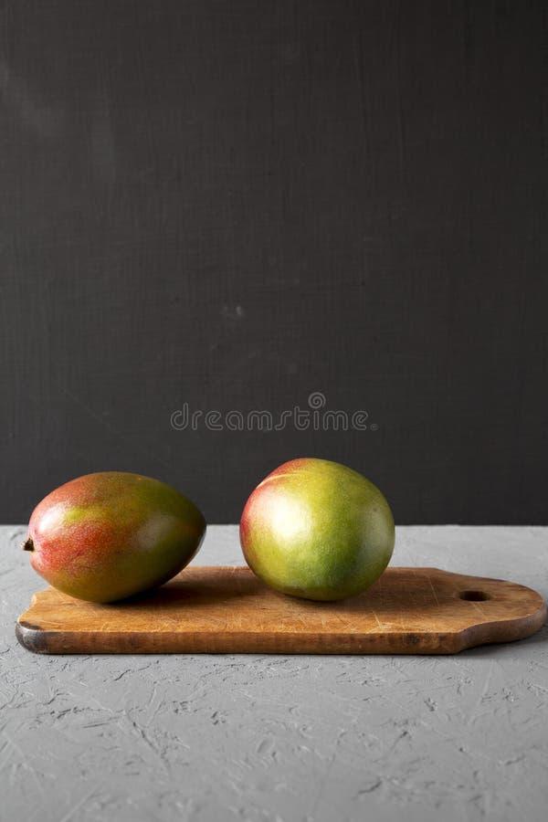 Zwei bunte süße Mangos auf rustikalem hölzernem Brett, Seitenansicht Kopieren Sie Platz stockbilder