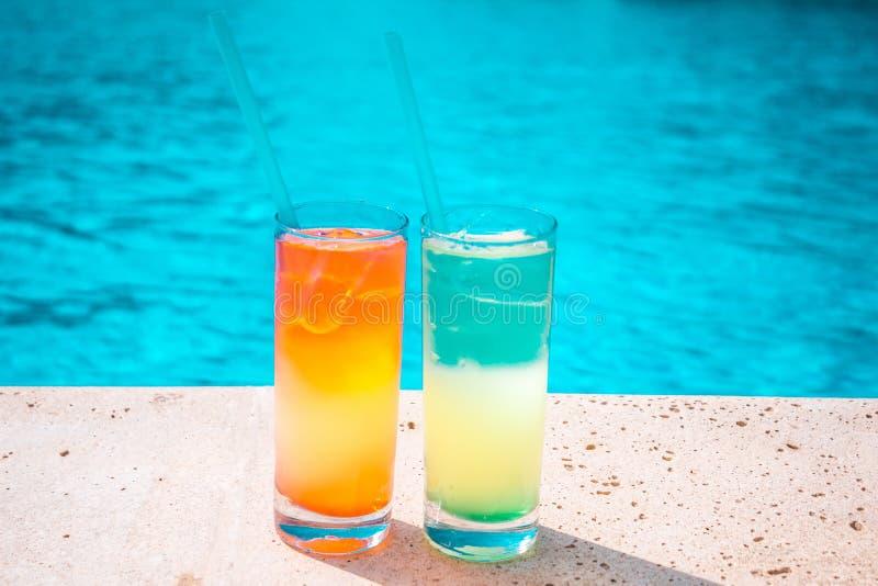 Zwei bunte tropische Cocktails auf dem Hintergrund des Pools Exotische Sommerferien stockfotografie