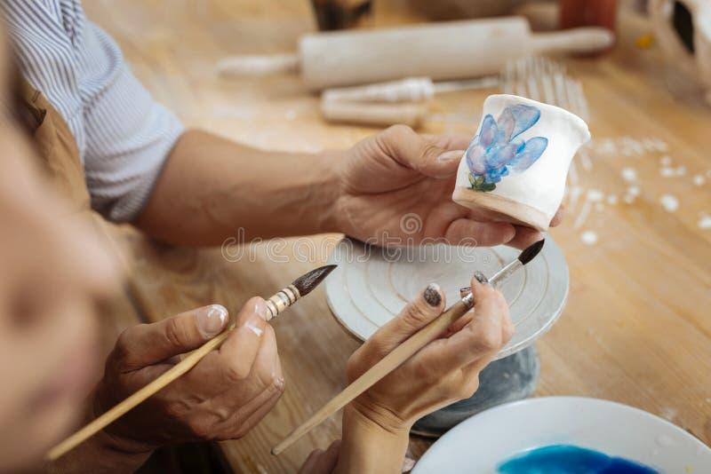 Zwei Ceramists, die Malereibürsten bei der Verzierung der Handarbeit halten lizenzfreie stockfotos