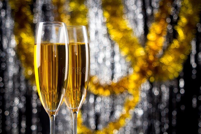 Zwei Champagner- oder Weingläser mit Gold- und Silberweihnachtslamettadekoration stockfotos