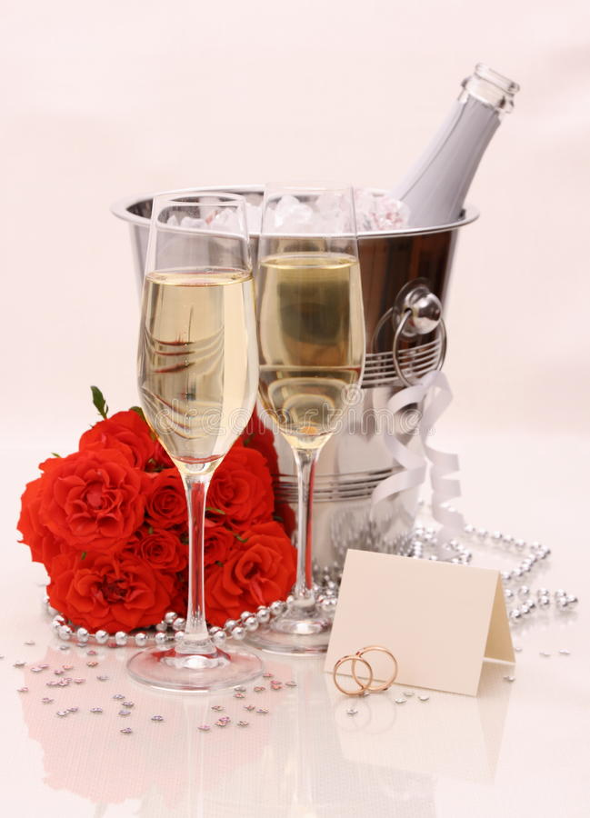 Zwei Champagnergläser, rote Rosen Goldene Hochzeits-Ringe stockfotografie