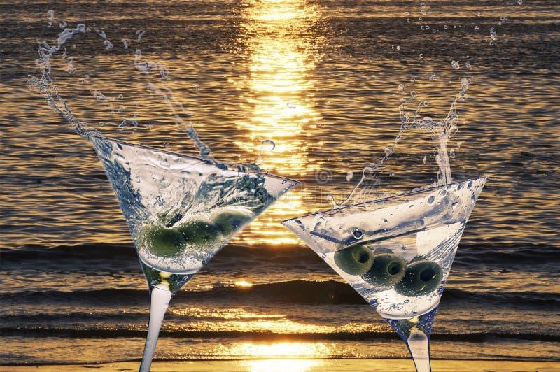 Zwei Cocktails mit dem Spritzen von Martini und von Oliven auf einem Sonnenuntergang beac stockfotos
