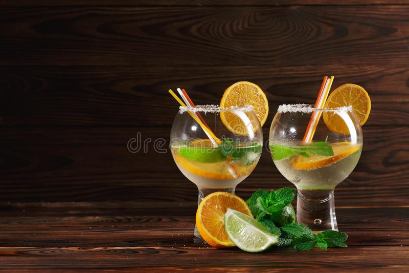 Zwei Cocktails mit Rum und Früchten Aperitiffrüchte und würzige Minze für ein kaltes Getränk Cocktails auf dem hölzernen Hintergr lizenzfreie stockbilder