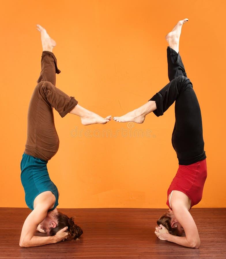 Zwei Damen in den Yoga-Kopf-Standplätzen lizenzfreie stockfotografie