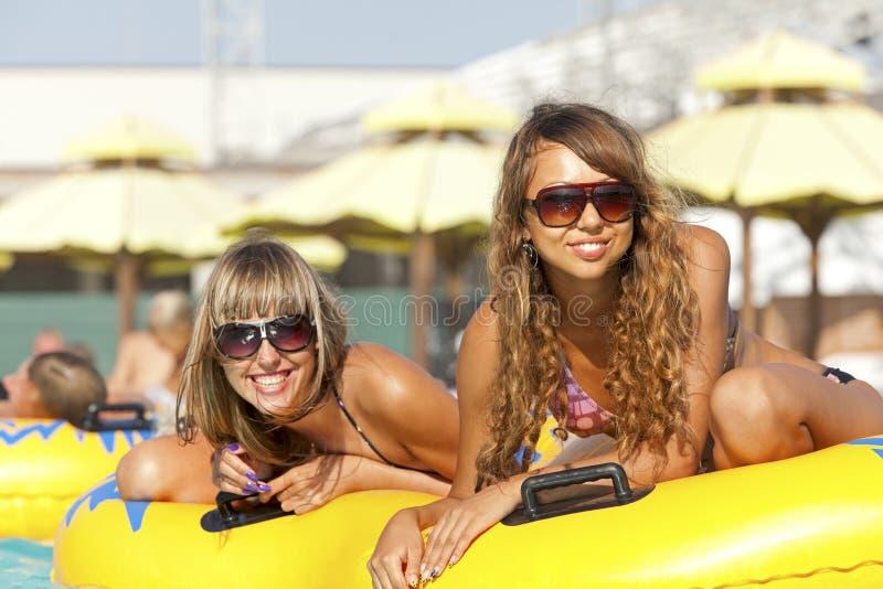Zwei Damen, die auf aufblasbarem Ring liegen stockbilder