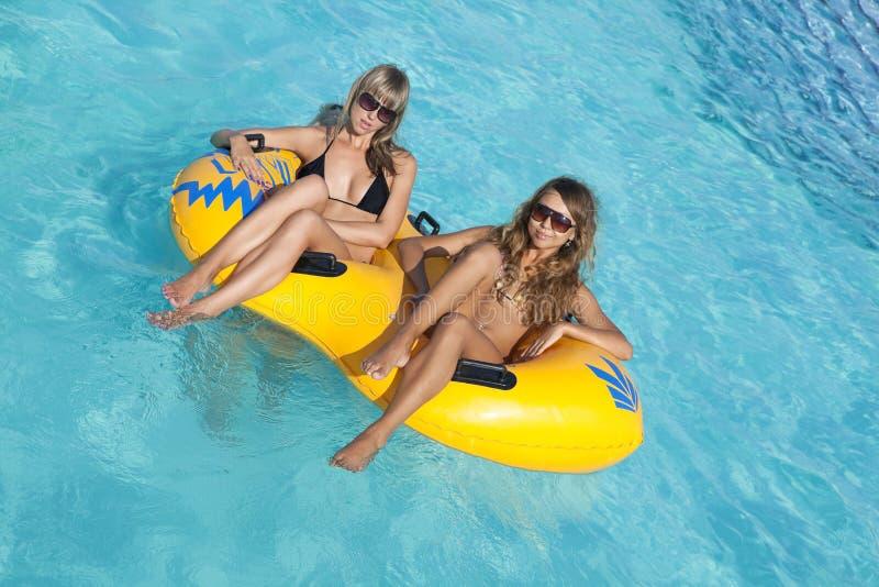 Zwei Damen, die auf aufblasbarem Ring liegen stockfotos