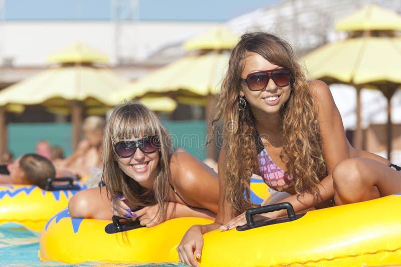 Zwei Damen, die auf aufblasbarem Ring liegen lizenzfreie stockfotografie
