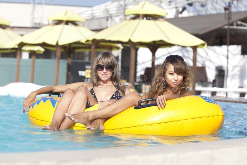 Zwei Damen, die auf aufblasbarem Ring liegen lizenzfreies stockfoto