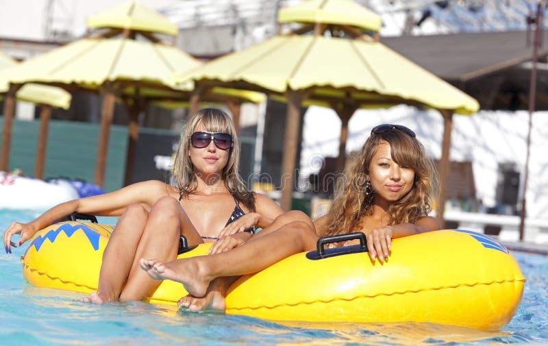 Zwei Damen, die auf aufblasbarem Ring liegen lizenzfreie stockbilder