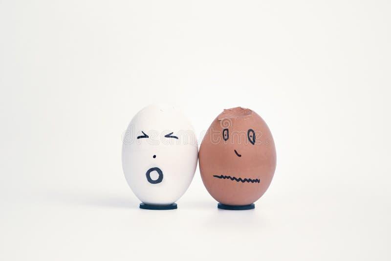 Zwei defekte Eier in Form von dem menschlichen Kopf, der auf einem Stand weiß und schwarz ist, beschweren sich miteinander lizenzfreies stockfoto