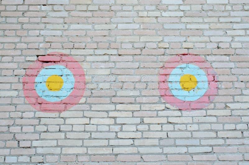 Zwei dekorative rot-blau-gelbe Kreise auf einer Backsteinmauer lizenzfreies stockbild