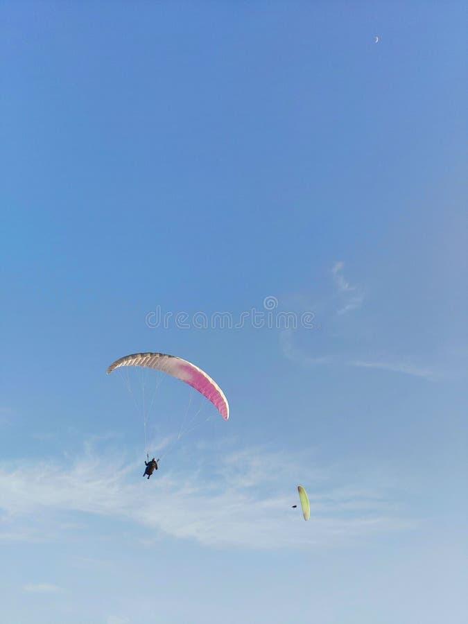 zwei die Fallschirme Rosa und Gelbes auf dem blauen Himmel des Hintergrundes stockfoto