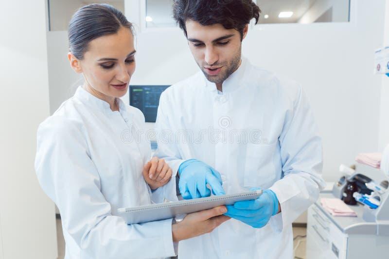 Zwei Doktoren als Team, das Tablet-Computer-Daten betrachtet lizenzfreie stockbilder