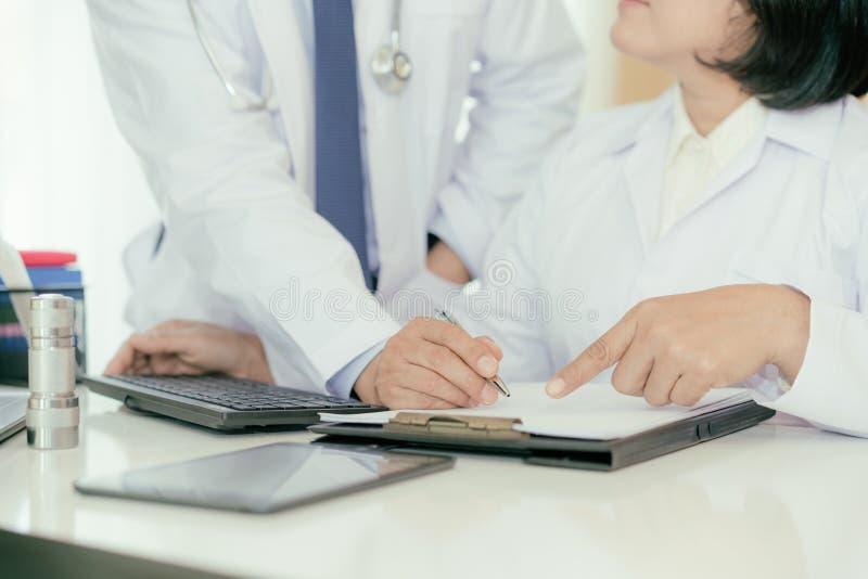 Zwei Doktoren, die über Krankenblatt im Modus analysieren und sich beraten lizenzfreie stockfotos