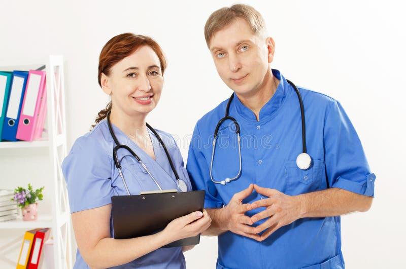 Zwei Doktoren, die in der Klinik des ?rztlichen Diensts, in Doktor und in der Krankenschwester, Krankenversicherung stehen lizenzfreie stockbilder
