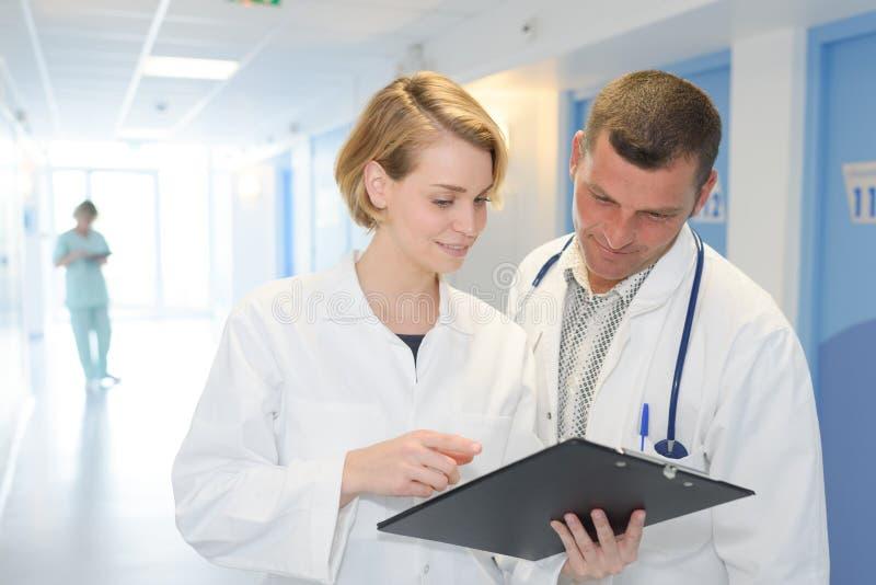 Zwei Doktoren mit Klemmbrett am Krankenhauskorridor lizenzfreie stockbilder