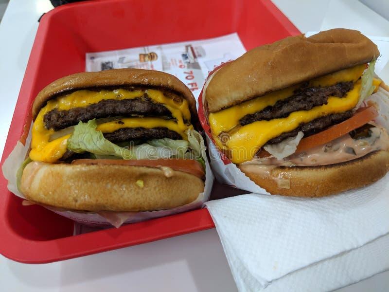 Zwei Doppel-doppelte Burger-Tierart am in--n-heraus Burgerrestaurant lizenzfreie stockfotos