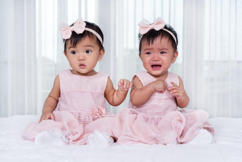 Zwei Doppelbabys im rosa Kleid auf Bett, eins, das, eins schreiend schaut stockfotografie