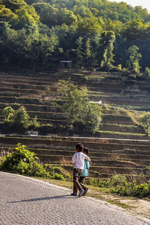 Zwei Dorfjungen, die an der Seite eines schmutzigen Weges nahe bei den Reisterrassen bei Yuanyang gehen lizenzfreies stockbild