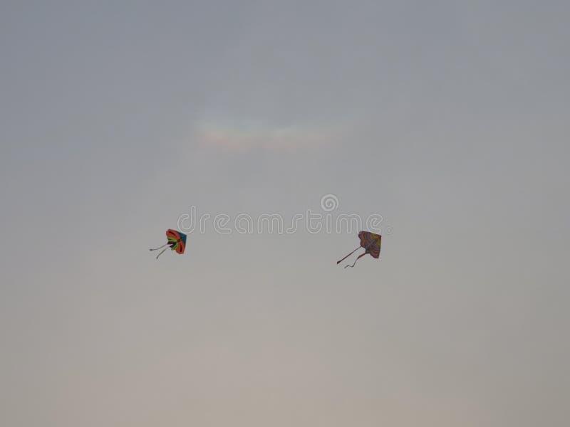 Zwei Drachen fliegen in den Himmel während der Zeit des Sunsettings lizenzfreie stockfotos