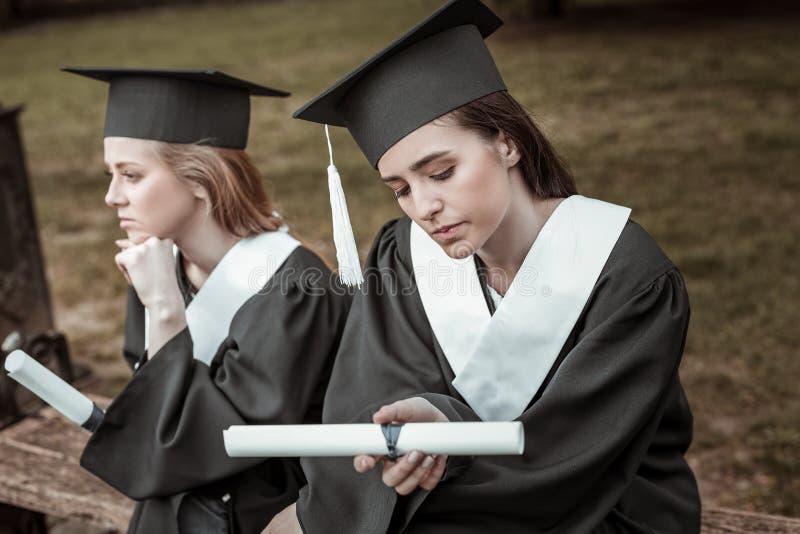 Zwei durchdachte Frauen, die auf Abschlussfeier warten stockfotografie