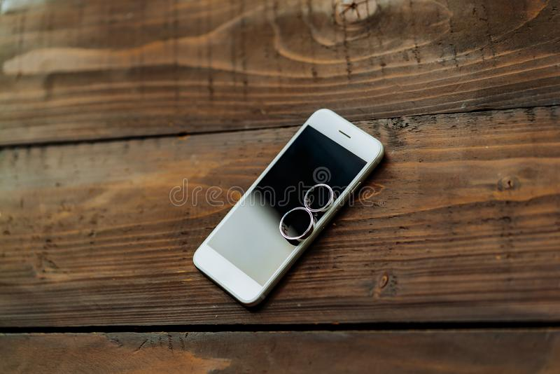 Zwei Eheringe legt an einem weißen Telefon auf dem Tisch Goldringe wurden für die Hochzeit gekauft stockfoto