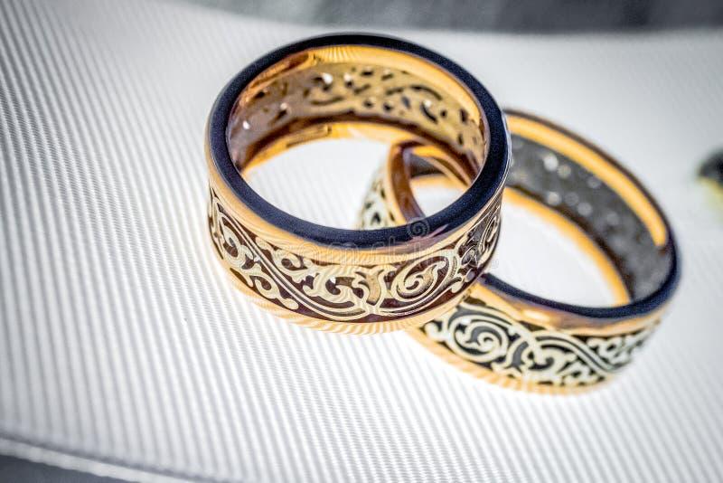 Zwei Eheringe mit seltenem Design auf weißem breitem Band stockfoto