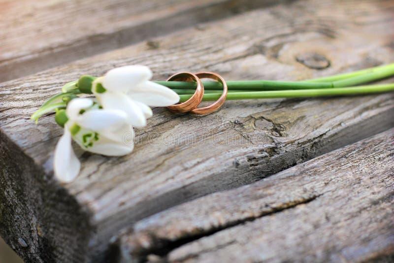 Zwei Eheringe und Blumen von Schneeglöckchen auf einem hölzernen rustikalen Ba lizenzfreie stockfotos