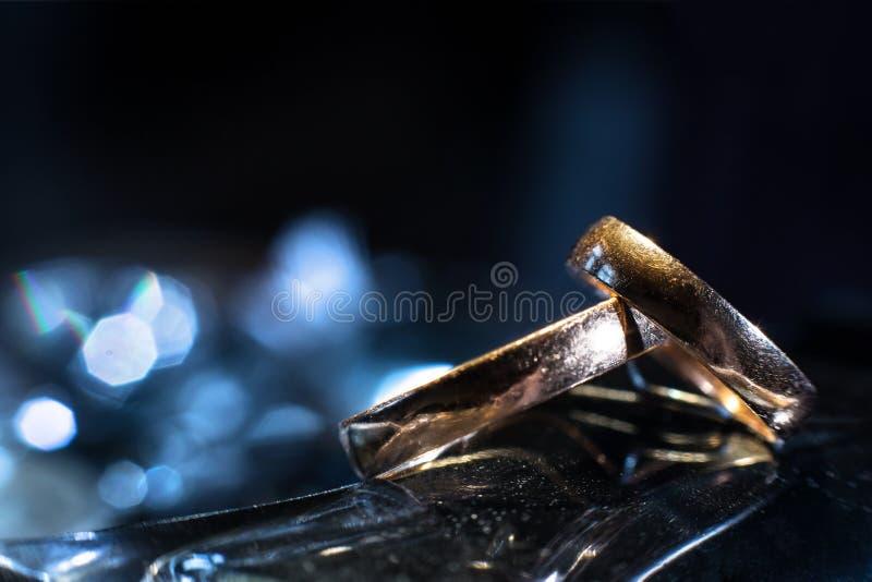 Zwei Eheringe von den verschiedenen Größen gemacht im Gold auf blauem bokeh Hintergrund stockfotos