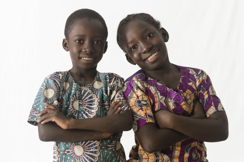 Zwei ehrfürchtige afrikanische Kinder, die mit den Armen aufwerfen, kreuzten, lokalisiert lizenzfreie stockfotografie