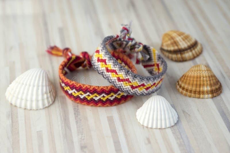 Zwei einfache handgemachte selbst gemachte natürliche gesponnene Armbänder Freundschaft auf weißen Holztisch- und Seeoberteilen stockfoto