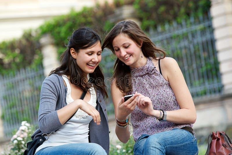 Zwei Einkaufenmädchen im Park mit einem Handy stockbild
