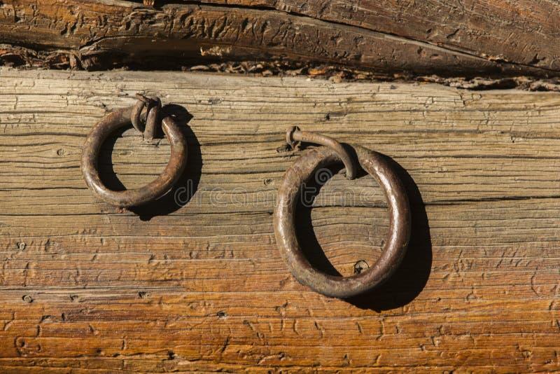 Zwei Eisenringe genagelt auf raues hölzernes Abstellgleis stockbild