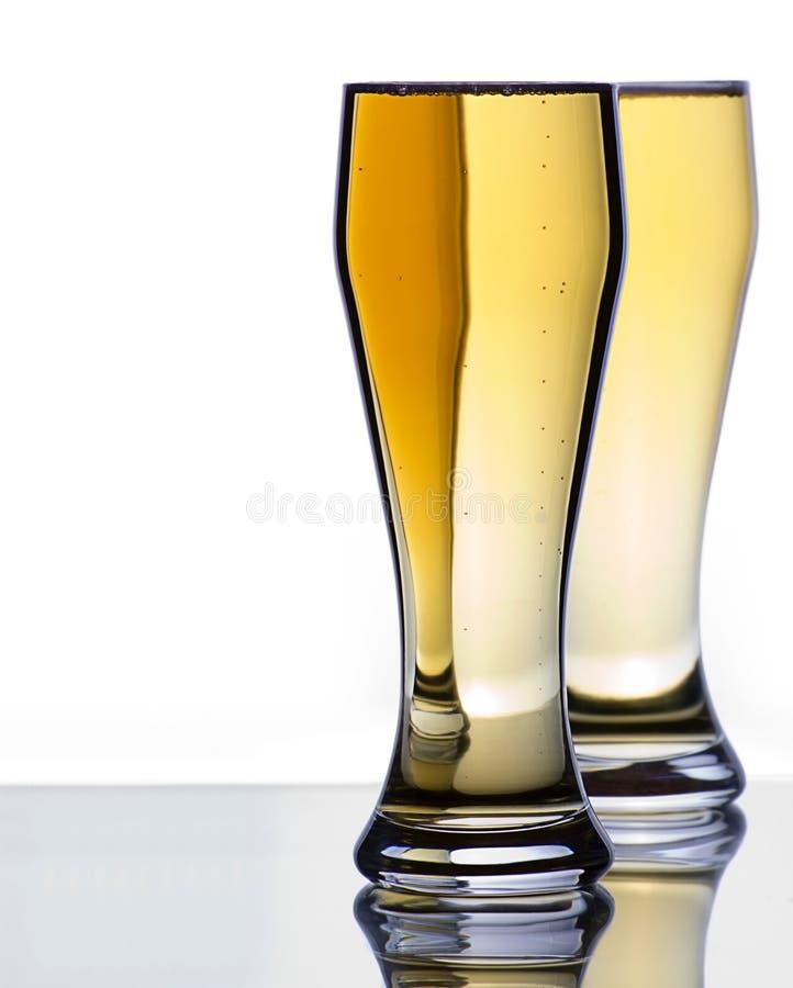 Zwei eiskalte Bier-Gläser auf reflektierender Oberfläche lizenzfreie stockfotos