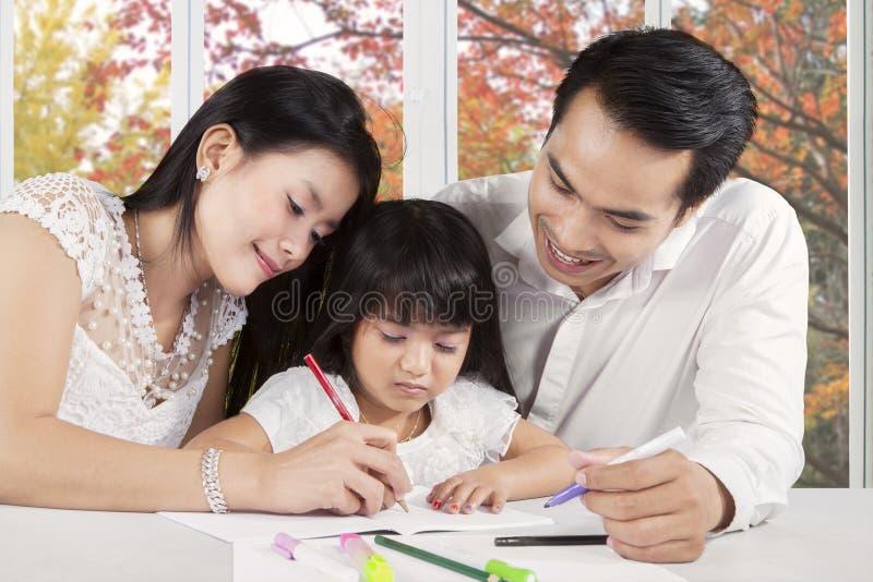 Zwei Eltern unterstützen ihr Kinderstudieren stockbild