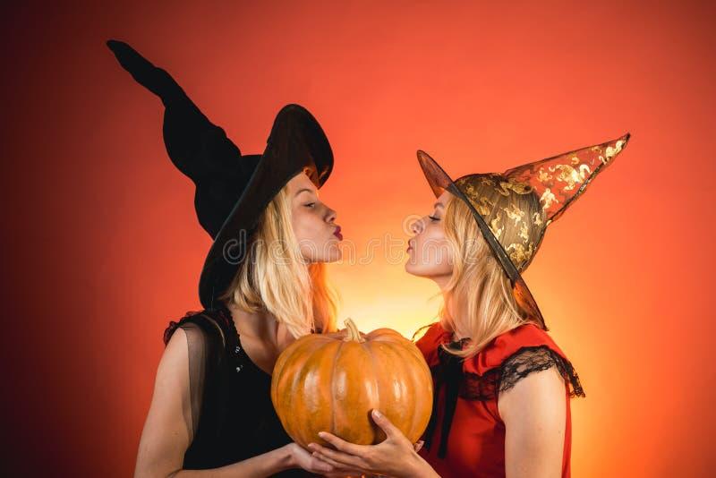 Zwei emotionale junge Frauen in Halloween-Kost?men auf Partei ?ber orange Hintergrund mit K?rbis Zwei Schönheiten herein lizenzfreies stockbild