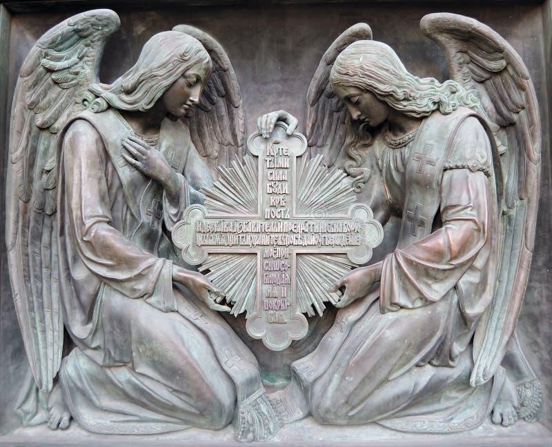 Zwei Engel halten Kreuz an stockfotografie