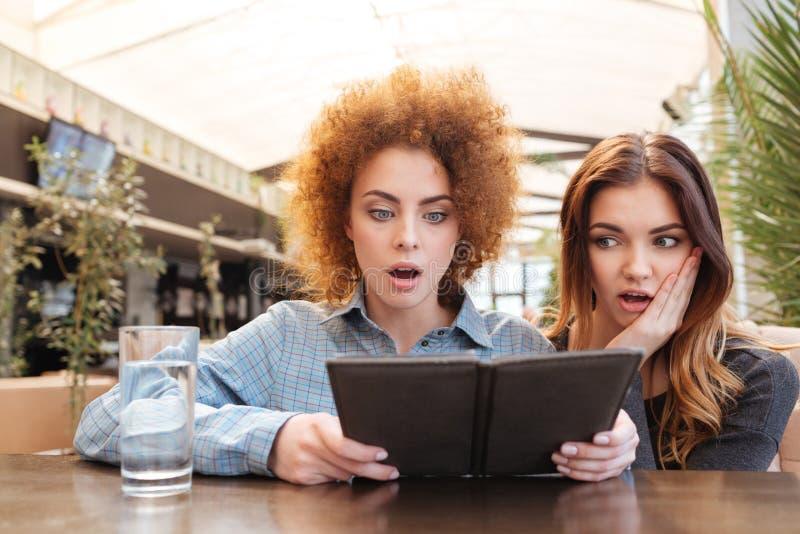 Zwei entsetzten die Frauen, welche die Rechnung im Café betrachten stockfotografie