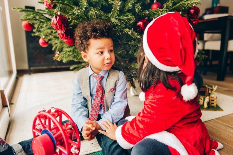 Zwei entzückende 3-Jährige Kinder, die durch den Weihnachtsbaum spielen lizenzfreie stockfotografie