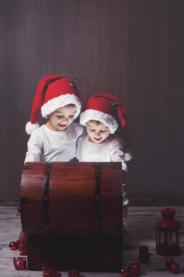 Zwei entzückende Jungen, öffnender hölzerner Kasten, glühendes Licht stockfotografie