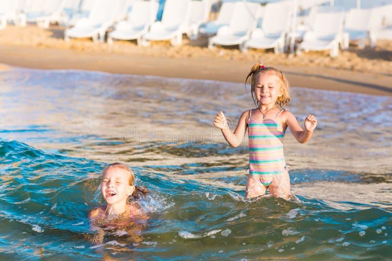 Zwei entzückende Kinder, die im Meer auf einem Strand spielen lizenzfreies stockbild