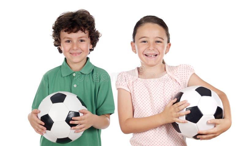 Zwei entzückende Kinder mit Fußballkugeln stockbild