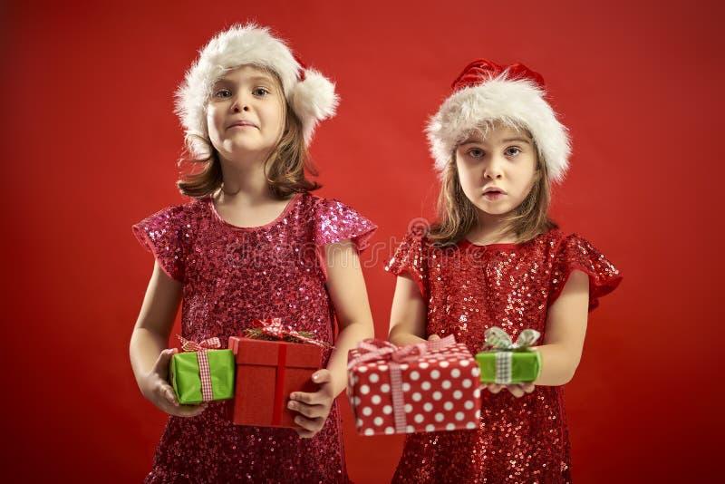 Zwei entzückende kleine Mädchen in einem Weihnachtskleid in einer Sankt Hut mit Geschenken lizenzfreie stockfotos