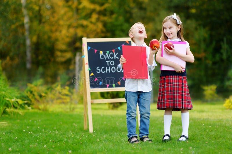 Zwei entzückende kleine Schulkinder, die über zur Schule zurück gehen aufgeregt glauben lizenzfreie stockfotos
