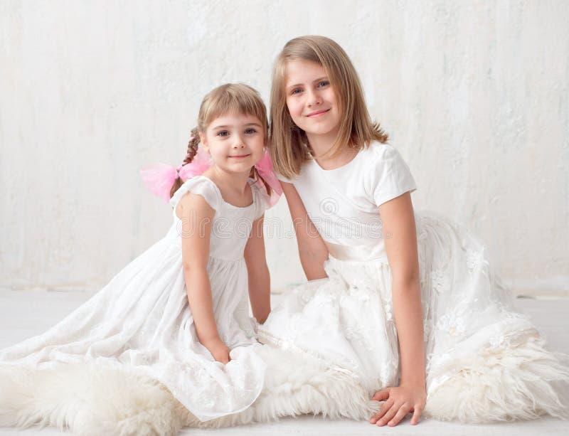 Zwei entzückende kleine Schwestern, die lachen und sich umarmen stockfotografie