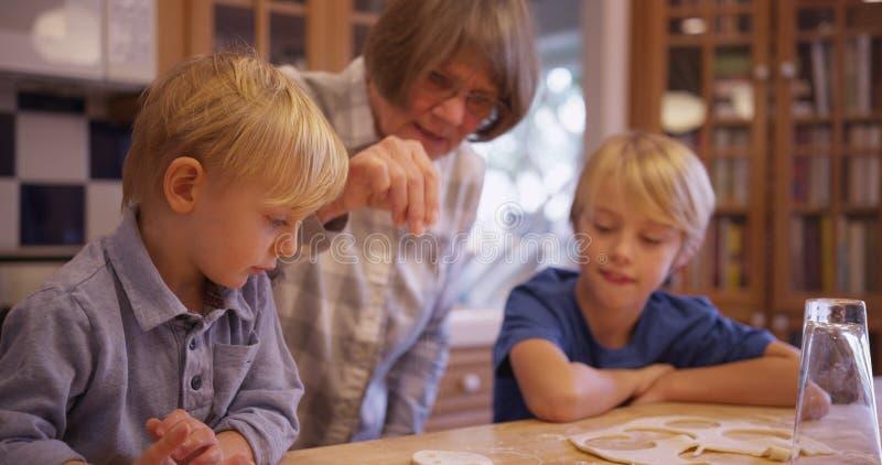 Zwei entzückende weiße Kinder, die Plätzchen mit Großmutter machen stockbilder