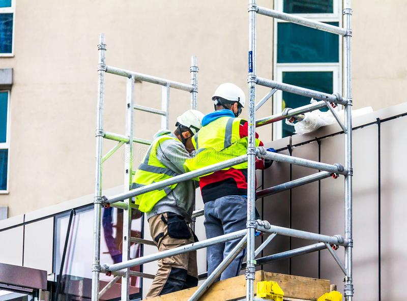 Zwei Erbauer in der Retro--reflektierenden Kleidung und Sturzhelme auf Baugerüst nehmen an Reparaturarbeit teil lizenzfreie stockfotografie