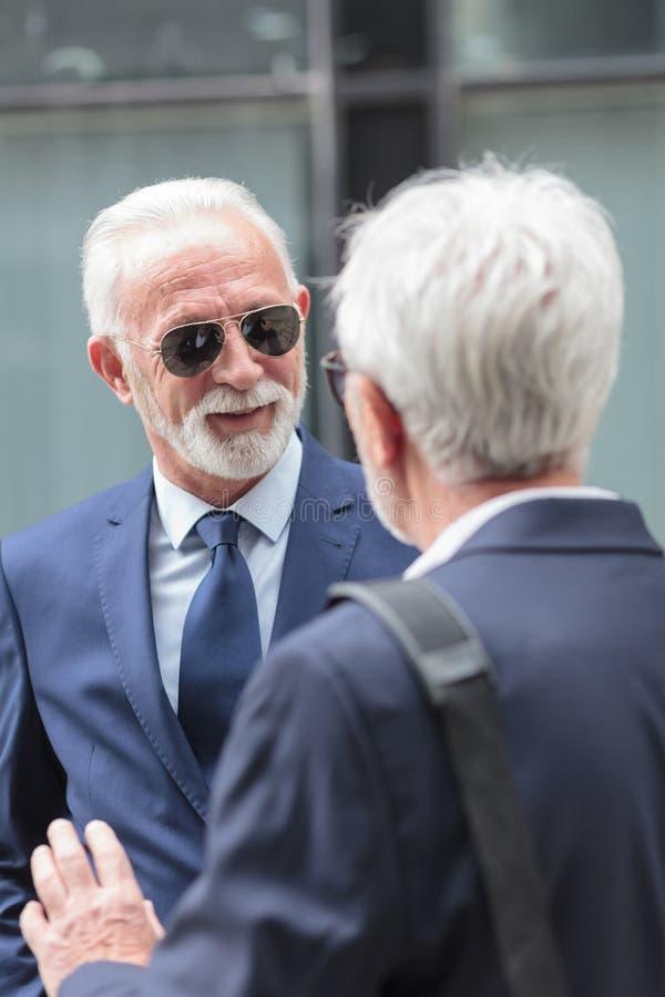 Zwei erfolgreiche erfahrene Führungskräfte in den Klagen sprechend vor einem Bürogebäude stockfotos